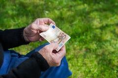 拿着欧洲钞票的老人的手 奋斗领抚恤金者概念 免版税库存照片