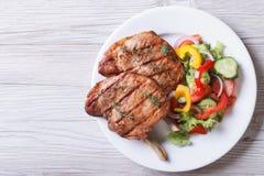 猪肉烤了有新鲜蔬菜沙拉顶视图 库存图片