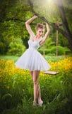 摆在与一个用花装饰的草甸的树摇摆附近的白色短的礼服的可爱的女孩在背景中 白肤金发的妇女年轻人 免版税图库摄影