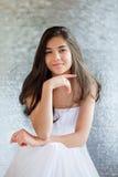 白色礼服开会的美丽的两种人种的青少年的女孩,认为 免版税库存照片