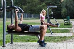 训练在室外健身房的人们 图库摄影