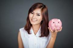 有一个桃红色猪钱箱的美丽的亚裔女孩 库存图片