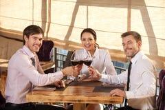 三个年轻朋友饮用酒一起在咖啡馆 免版税库存照片