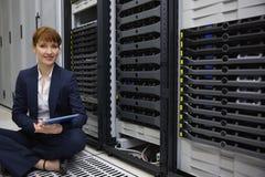 技术员坐在服务器塔旁边的地板使用片剂个人计算机 免版税库存图片