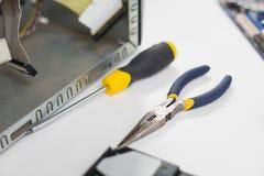 在残破的设备旁边的计算机工程师工具 图库摄影