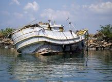 在海滩的腐烂的渔夫小船在早晨光 免版税库存照片