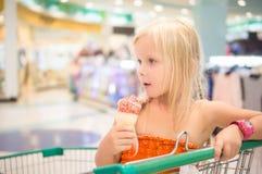 Το λατρευτό κορίτσι τρώει το παγωτό φρούτων με το ουράνιο τόξο ψεκάζει στο κατάστημα Στοκ εικόνες με δικαίωμα ελεύθερης χρήσης