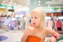 Το λατρευτό κορίτσι τρώει το παγωτό φρούτων με το ουράνιο τόξο ψεκάζει στο κατάστημα Στοκ Εικόνες