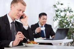 吃午餐的繁忙的商人在办公室 免版税库存照片