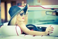驾驶一辆敞篷车红色减速火箭的汽车的时髦的白肤金发的葡萄酒妇女室外夏天画象  时兴的可爱的公平的头发女孩 免版税库存照片