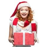 拿着礼物的圣诞老人帽子的可爱的快乐的少妇 免版税库存照片