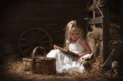 有一只小猫的女孩在干草 免版税库存照片