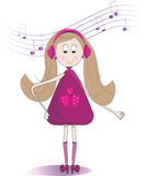 在耳机的逗人喜爱的小女孩听的音乐 免版税图库摄影