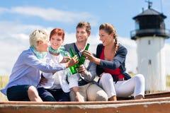 喝被装瓶的啤酒的朋友在海滩 免版税图库摄影