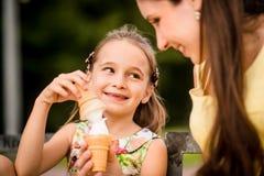 享用冰淇凌的母亲和孩子 库存图片