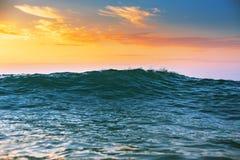 日出轻发光在海浪 库存照片