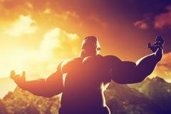 Μυϊκό ισχυρό άτομο με το ήρωα, αθλητική μορφή σωμάτων που εκφράζει τη δύναμη και τη δύναμή του Στοκ Φωτογραφία