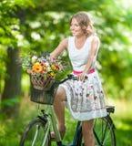 穿一件精密白色礼服的美丽的女孩获得乐趣在有自行车的公园 健康室外生活方式概念 葡萄酒风景 免版税库存图片