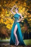 蓝色礼服的时兴的美丽的少妇在背景中的摆在室外生锈的森林 有庄重装束的可爱的女孩 免版税库存图片
