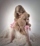 拿着玩具熊的哀伤的小女孩 库存图片