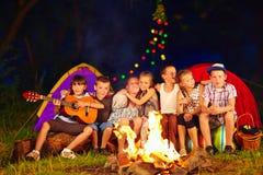 唱歌曲的愉快的孩子在阵营火附近 库存图片