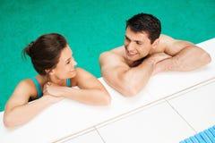 夫妇松弛近的游泳池 库存照片
