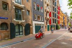 在阿姆斯特丹街道上的骑自行车者  免版税库存照片