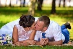 愉快的新娘和新郎在他们的婚礼在草说谎在公园和亲吻 免版税库存照片