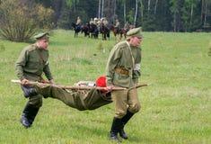 医疗小队的人移动一位受伤的战士 免版税库存照片