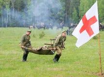 医疗小队的人移动一位受伤的战士 图库摄影