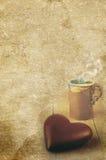 巧克力心脏和一个杯子在老葡萄酒构造了纸背景 免版税库存图片