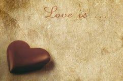 在老葡萄酒的巧克力心脏构造了纸背景 库存照片