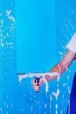 与橡皮刮板的播种的图象仆人清洗的玻璃 免版税库存照片