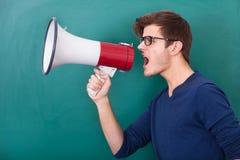 呼喊在扩音机的年轻人 免版税库存照片