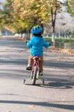 骑他小的自行车的年轻男孩 库存图片