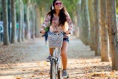 相当女孩骑马自行车和听到音乐 免版税库存图片