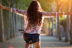相当女孩骑马自行车在森林里 免版税库存图片