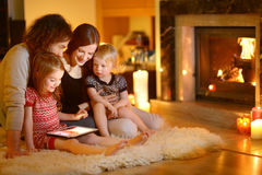 使用一台片剂个人计算机的愉快的家庭由壁炉 库存照片