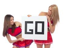 啦啦队员从啦啦队欢呼队的舞蹈家女孩拿着标志 免版税图库摄影