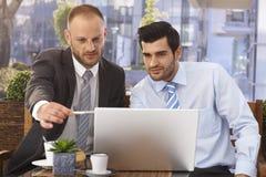 研究膝上型计算机的商人在室外咖啡馆 免版税库存照片