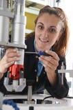 Θηλυκός μηχανικός μαθητευόμενων που εργάζεται στη μηχανή στο εργοστάσιο Στοκ Εικόνες