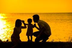 亚洲家庭室外日落海滩 免版税库存图片