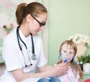 医生藏品孩子呼吸的吸入器屏蔽 免版税库存图片