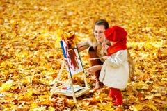 在画架的母亲和儿童图画在秋天停放 创造性的孩子 免版税库存照片