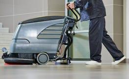 工作者与机器的清洁地板 免版税库存照片