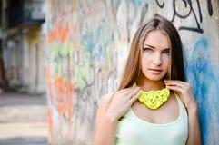 关闭获得美丽的时髦的时尚的女孩画象轻轻地微笑和看在街道画城市墙壁上的乐趣照相机 免版税图库摄影