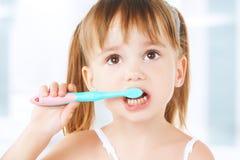 刷她的牙的愉快的小女孩 图库摄影