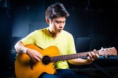 演奏音乐的亚裔吉他弹奏者在录音室 免版税库存图片