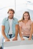 使用他们的膝上型计算机的愉快的夫妇 免版税库存照片