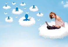 坐在与膝上型计算机的云彩的少妇 免版税库存照片